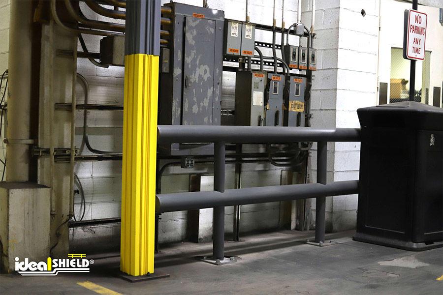 Ideal-Shields-Yellow-and-Gray-Square-Column-Wraps-stacked-on-top-on-one-another-next-to-standard-guardrail