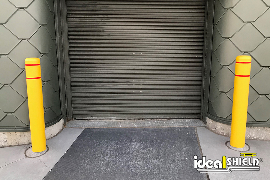 Ideal Shield's Yellow Flat Top Bollard Covers with Red Reflective Tape guarding an overhead door