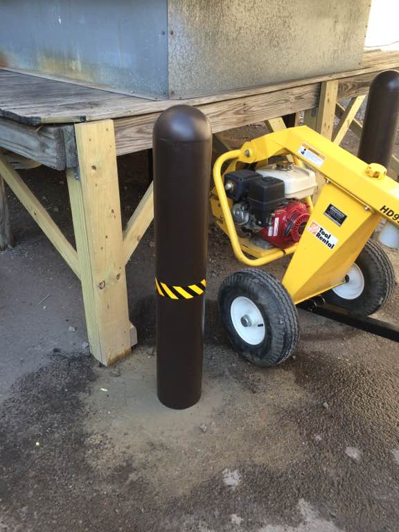 Ideal Shield's black bollard cover with caution tape at a construction site