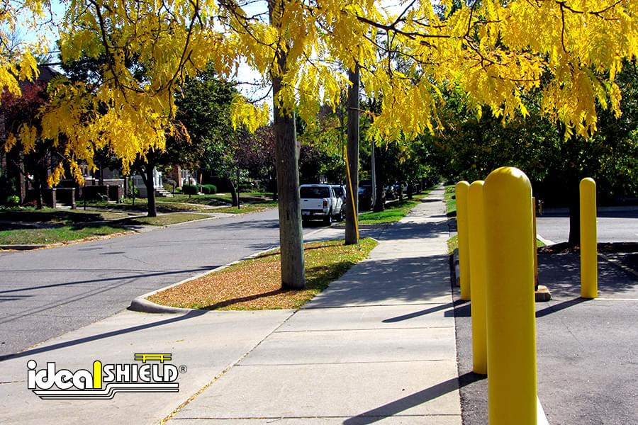 "Ideal Shield's Yellow 1/4"" Bollard Covers guarding a parking lot."