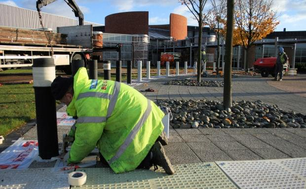 Painter preparing bollards for a new paint job.