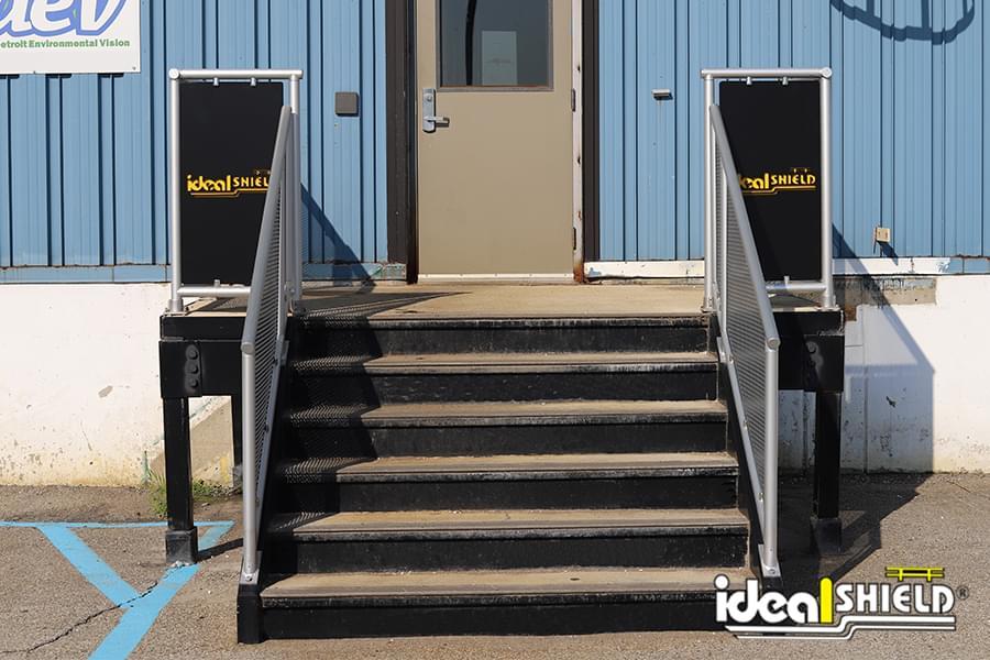 Custom infill panels for aluminum handrail with Ideal Shield's logo