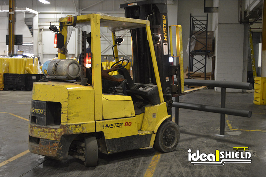 Forklift installing Ideal Shield's Gray Guardrail