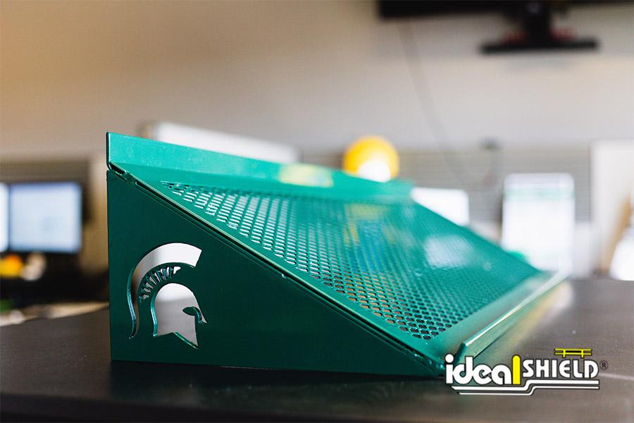 Custom cut metal art of a Michigan State Spartan head shoe shelving unit designed to hang in a locker room