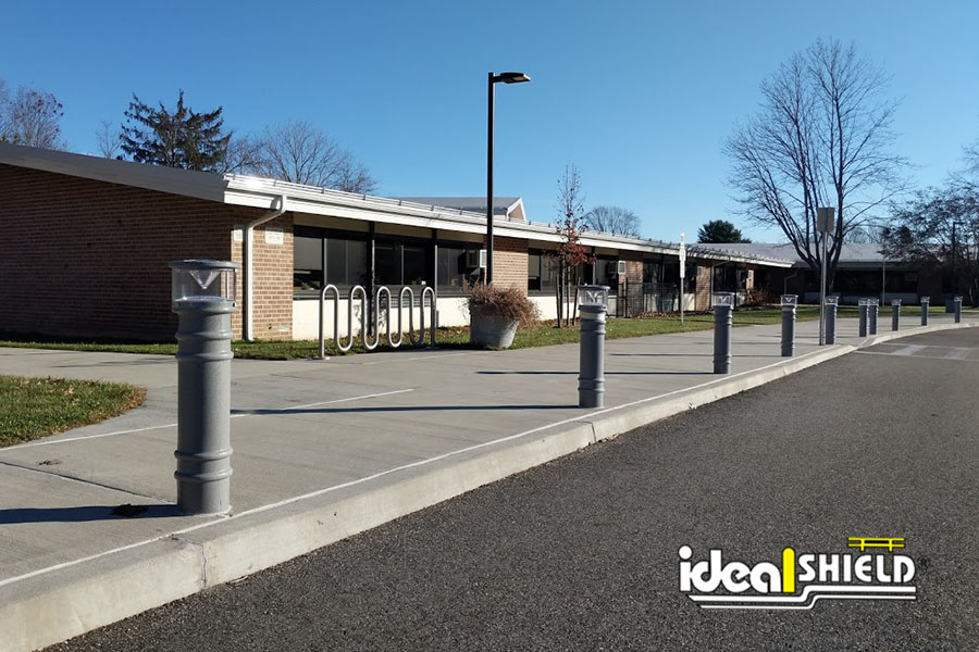 Ideal Shield's UV Lighted Bollard Covers lining a school entrance