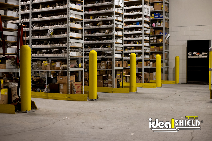 "Ideal Shield's 8"" Base Plate Bollards protecting storage racks from forklift traffic"